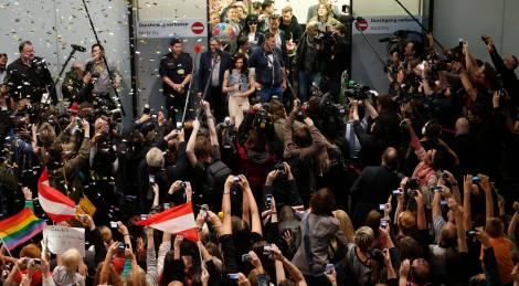 Austria's Conchita Wurst arrives with her trophy at Vienna's airport